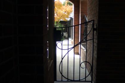 背面から眺める通路に佇む門扉